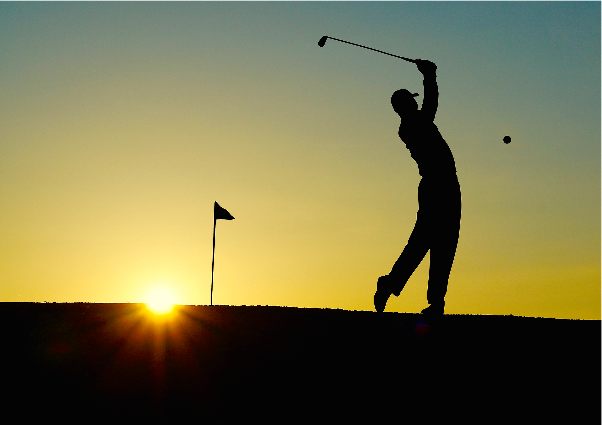 silhouette of golfer in front of sunset